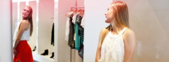 Giovane donna in piedi di fronte a uno specchio mentre si sta provando degli abiti nuovi. L'immagine illustra come cambia il corpo di una giovane donna durante la pubertà.