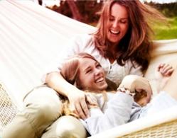 Foto di due donne sorridenti sdraiate su un'amaca.