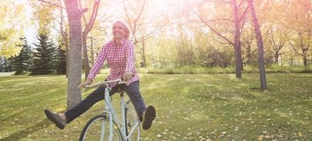 Foto di una donna in bicicletta. L'immagine illustra una donna attiva e in forma, anche durante il ciclo.