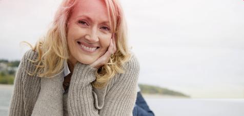 Foto con inquadratura a sinistra di una donna di mezza età che sta sorridendo.