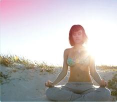 Foto di una donna seduta in meditazione sulla spiaggia. L'immagine illustra che è possibile rilassarsi e vivere normalmente anche durante il ciclo.