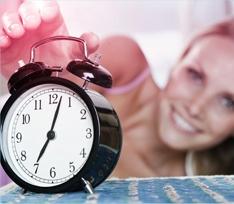 Foto di una sveglia con una donna sullo sfondo che allunga un braccio per spegnere la suoneria.