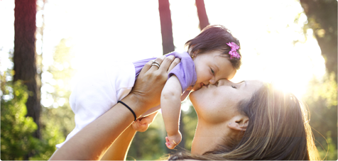Immagine di una donna che solleva e bacia una bambina.