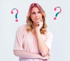 Foto di una donna dubbiosa con punti di domanda sulla sfondo. L'immagine illustra che è comune porsi molte domande sulle mestruazioni, alle quali o.b.® ha cercato di rispondere qui.
